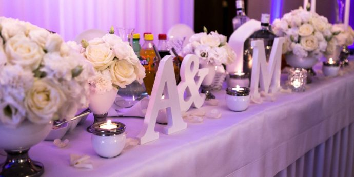 Litery na stole i białe kwiaty