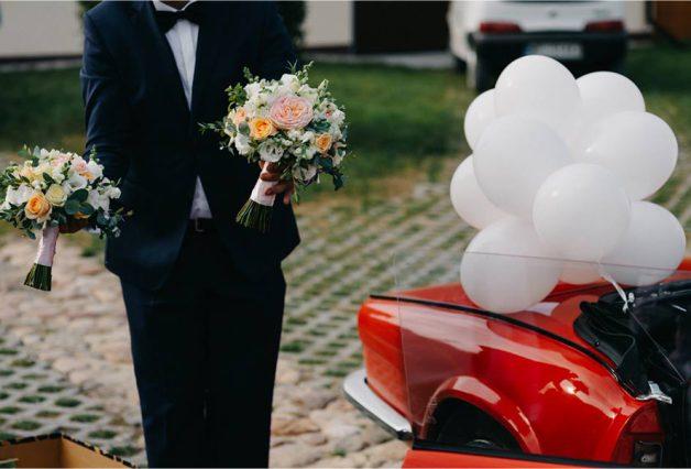 Białe balony na czerwonym samochodzie